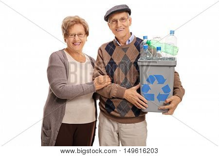 Cheerful mature couple posing with a recycling bin full of plastic bottles isolated on white background