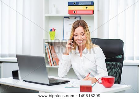 Beautiful girl in the office. He is sitting at a table with a laptop