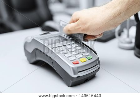 Bank terminal and a man's hand with a credit or debit card to make payments.
