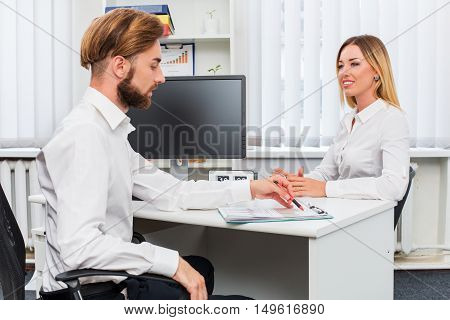 man and a woman being interviewed in the office. at table with computer