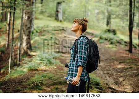 Woman Traveler With Backpack And A Bottle Of Water In A Forest