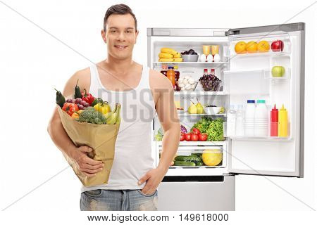 Man posing with a shopping bag full of groceries in front of an open fridge isolated on white background