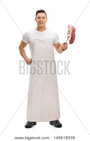 Full length portrait of a joyful butcher holding a fork with a steak isolated on white background