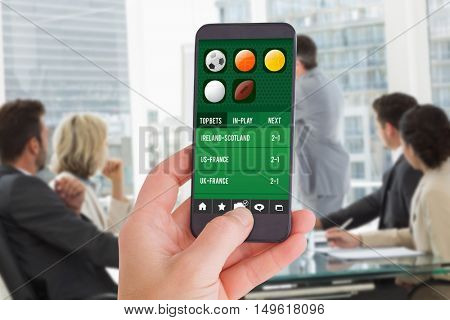 Female hand holding a smartphone against business people in office at presentation