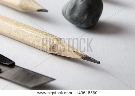 Pencil Closeup With Kneaded Eraser, And Cutter Knife, On Blank White Sheet Of Paper