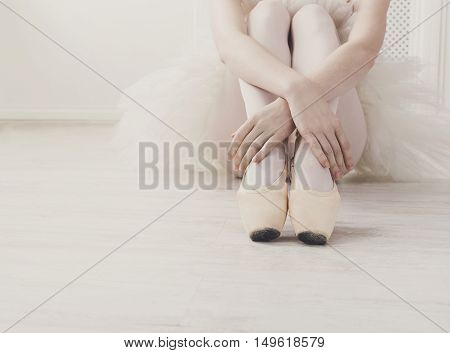 Closeup of young ballerina legs, sit in pointe shoes at white wooden floor background, with copy space. Ballet practice. Beautiful slim graceful feet of ballet dancer.