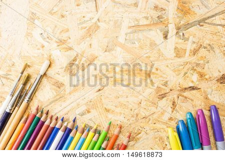 Bunch Of Colorful Pencils Markers And Paint Brushes, On Flakeboard Surface With Copy-space.