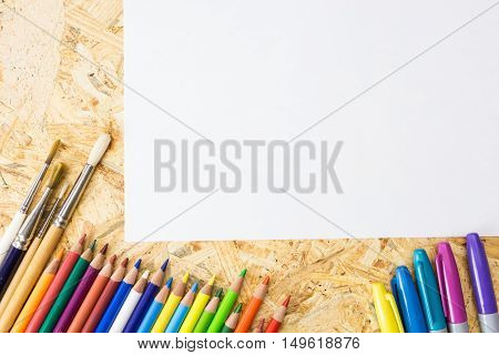 Bunch Of Colorful Pencils, Markers And Paint Brushes, With Blank Sheet Of Paper, On Wooden Surface