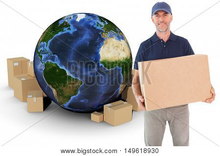 Happy delivery man holding cardboard box against globe and cardboard boxes