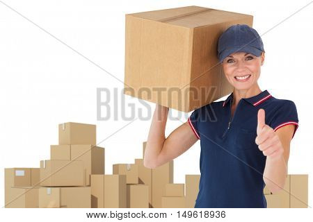 Happy delivery woman holding cardboard box showing thumbs up against cardboard boxes over white background