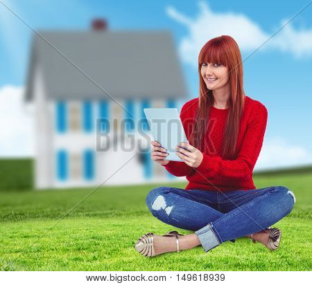 Smiling hipster woman sitting on the floor against house in the distance