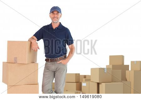 Happy delivery man leaning on pile of cardboard boxes against arrangements of cardboard boxes