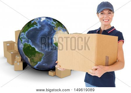 Happy delivery woman holding cardboard box against globe surrounded by cardboard boxes
