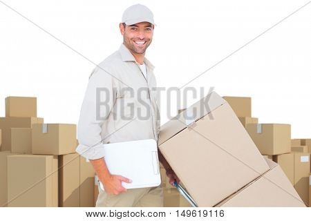 Delivery man pushing trolley of boxes on white background against arrangements of cardboard boxes