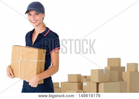 Happy delivery woman holding cardboard box against arrangements of cardboard boxes