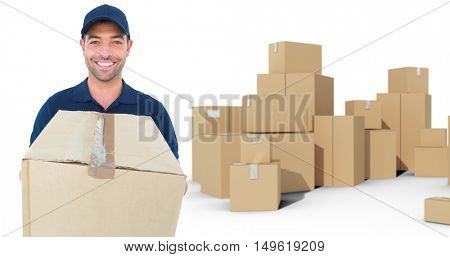 Happy delivery man holding cardboard box against cardboard boxes over white background