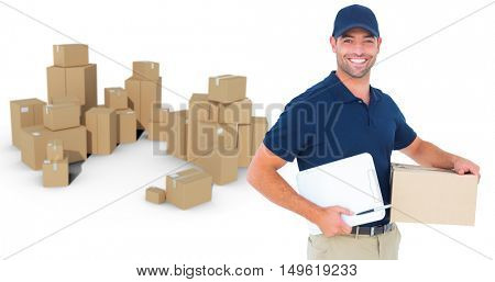 Happy delivery man with cardboard box and clipboard against stack of cardboard box on white background