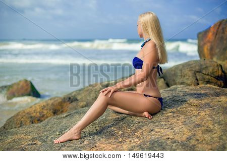 Beautiful blonde woman in the blue bikini with perfect legs posing on the lonely rock in the ocean