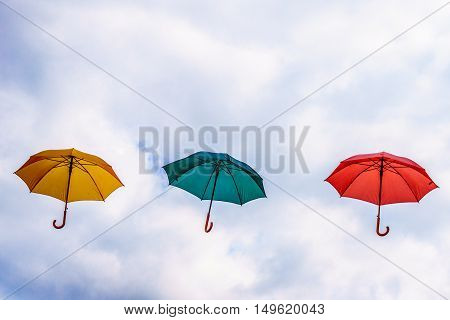 Yellow Umbrella, Green Umbrella and Red Umbrella floating in the Air under Cloudy Sky