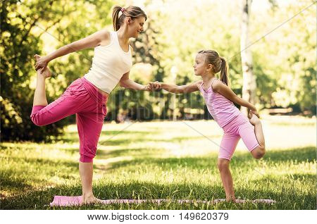 Mother and daughter have yoga class in the park.