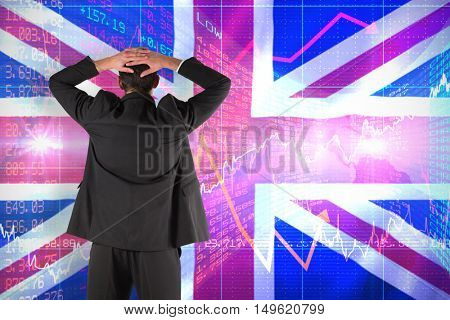 Businessman standing back to the camera with hands on head against digitally generated uk national flag
