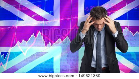 Stressed businessman with hands on head against digitally generated uk national flag