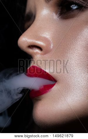Beautiful sexy brunette girl with bright makeup red lips smoking with smoke from mouth. beauty face. Photos shot in the studio on a black background.