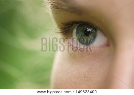 close up photo of beautiful green young female eye outdoors, focus on pupil
