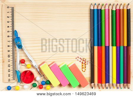 Colorful pencils with bright writing-materials over wooden surface