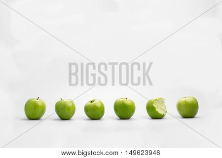 Row of whole healthy fresh green apples with one eaten or bitten into in a conceptual image against a white background with copy space