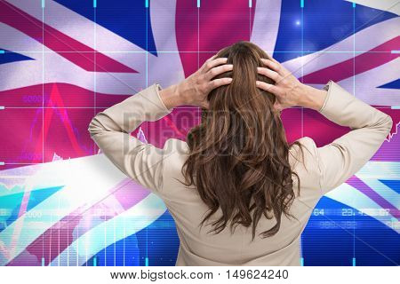 Young classy businesswoman with hands on head standing back to camera against digitally generated great britain national flag