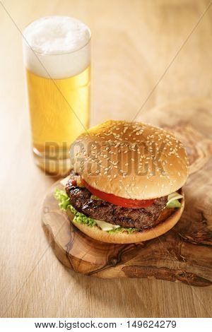 fresh juicy burger with lager beer on oak table, wide angle shot
