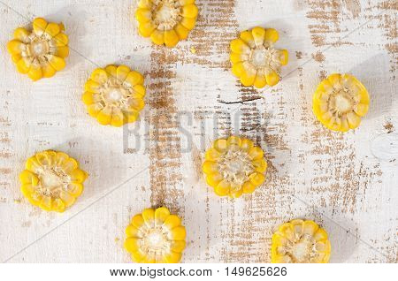 pieces of corn on white wooden background.