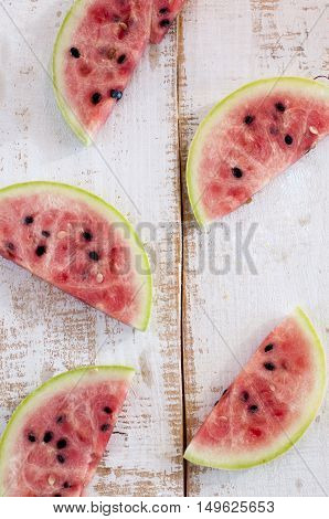 lices of pink watermelon on a wooden background