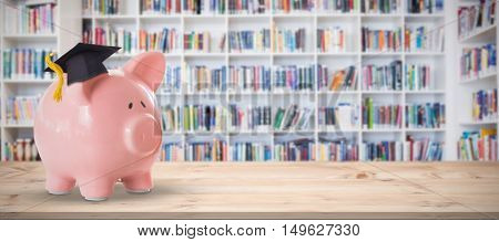 Piggy bank with graduation hat against teacher reading books to her students