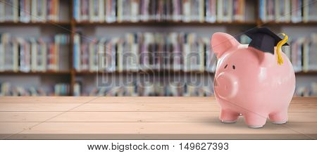 Piggy bank with graduation hat against library shelf