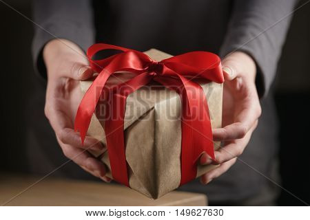 female teen girl shows paper gift box with red ribbon and a bow, shallow dof