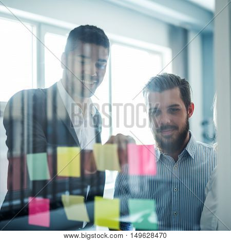 Businesspeople looking at the sticky notes in an office.