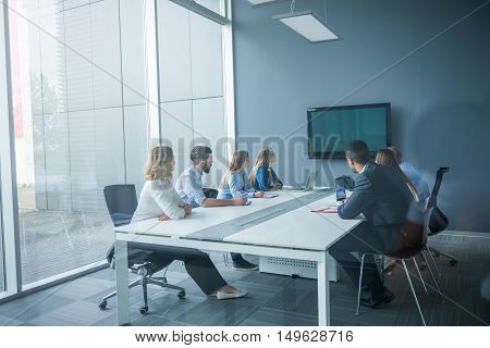 Businesspeople watching presentation in a conference room.