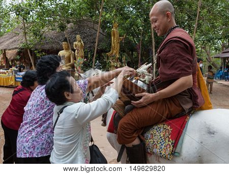 Chiang Rai, Thailand - May 21, 2016: Buddhist Monk Receiving Alms From Local People In Golden Horse