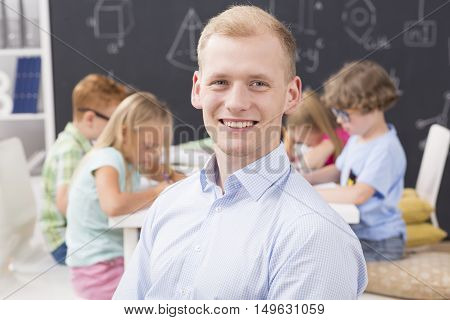 Shot of a smiling young teacher and his primary school students sitting in the background