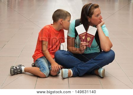 mother and son sitting on the floor with the tickets for the flight