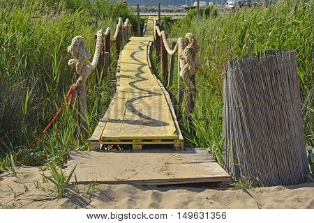 A wooden walkway across a marshy area next to a beach on the Croatian coast near Blace.