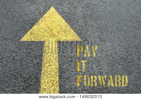 Yellow forward road sign with Pay It Forward word on the asphalt road. Business concept.