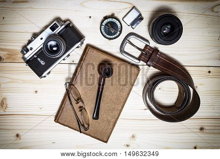 Still life with retro object. Book with compact old camera compass cigarette lighter belt glasses pipe dslr lens on wood table.