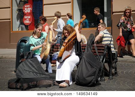 Lvov Ukraine - July 22 2016: Street musicians on Market Square one of the most famous and busiest shopping square in Ukraine. Girls playing on bandura. Bandura - ukrainian folk stringed musical instrument