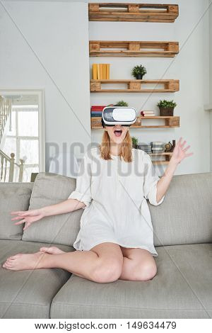 The girl in white sitting on a grey sofa in a virtual reality helmet