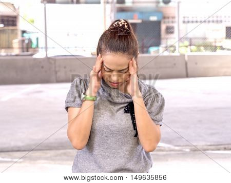 Headache migraine people, emotions, stress and health care concept - unhappy asia woman touching her head and suffering from headache.