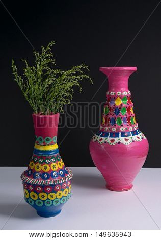 Still life of two artistic painted colorful handcrafted pottery vases and green plant branches with harsh shadow on white table and black wall