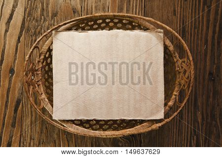 wicker basket with paper sheet inside on a wooden table